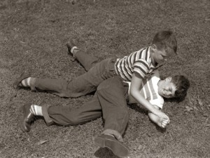 1950s-two-boys-wear-tee-shirts-blue-jeans-playing-rough-fighting-wrestling-on-the-grass