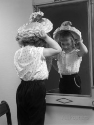 1950s-little-girl-trying-on-hat-looking-into-mirror-reflection