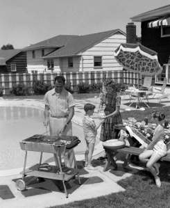 1950s Family In Backyard Beside Pool Having Cookout Of Hot Dogs and Hamburgers