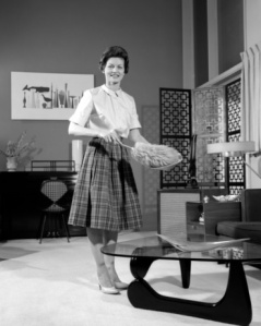 Woman-Wearing-A-White-Blouse-Plaid-Skirt-Dusting-A-Bowl-With-A-Feather-Duster-In-Front-Of-A-Glass-Top-Coffee-Table-Smiling-Modern-Living-Room