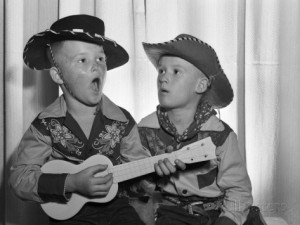 d-corson-1950s-2-juvenile-boys-in-cowboy-hat-and-shirts-playing-ukulele-and-singing-mouth-open-wide