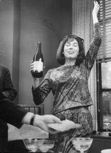 COSMOPOLITAN editor Helen Gurley Brown ecstatically hoisting a bottle of champagne